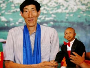 Nice to meet you... the world's tallest man, Bao Xishun (left), shakes hands with He Pingping, who only measures 72 centimetres.